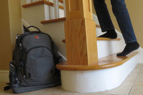 Backpack sitting at base of stairs as teen climbs up stairs