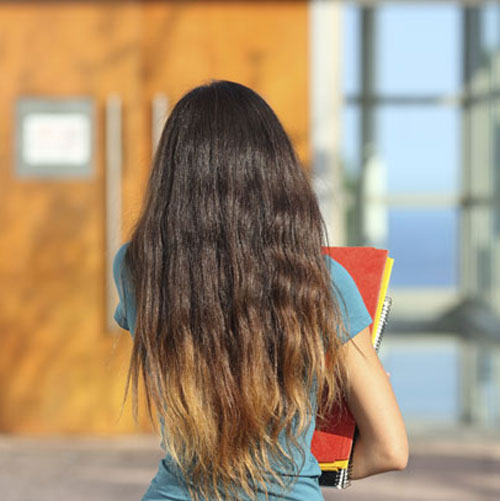 Back of teen carrying books facing door