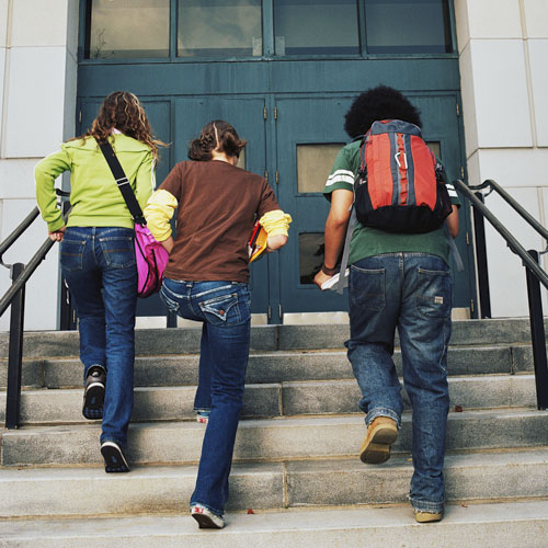 Backs of three students walking up steps to front door of school