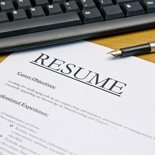 Closeup of printed resume beside keyboard and pen